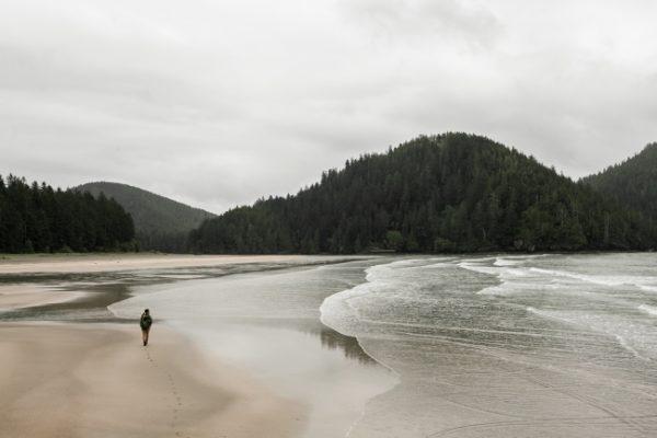 A man walks along the shore of the beach under an overcast sky.