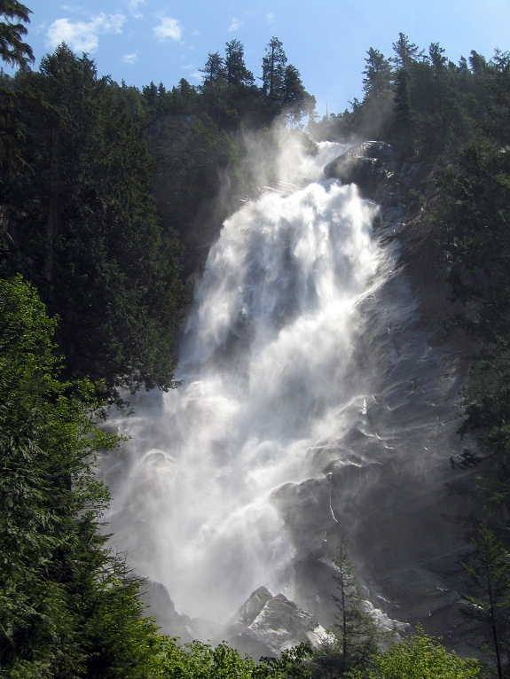 Shannon Falls cascading down with lush green trees surrounding the falls and blue skies above.