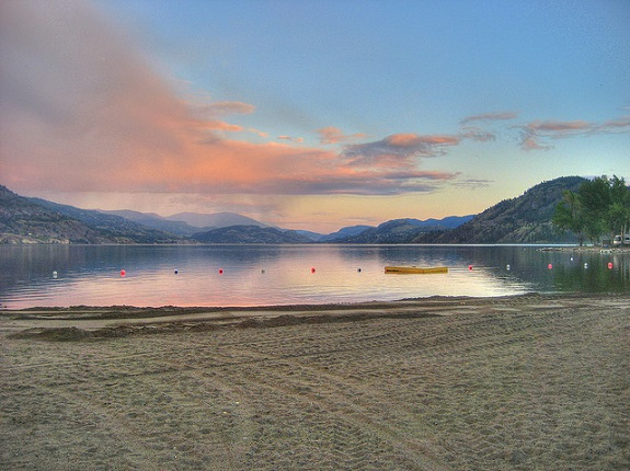 Skaha Lake with the sandy beach in the foreground and glass-like lake in the background and a pink sunset above.
