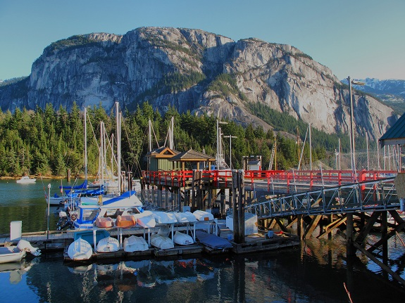 A wooden dock with red railings and colourful sailboats floating in the Squamish harbour, with the Stawamus Chief looming in the background.