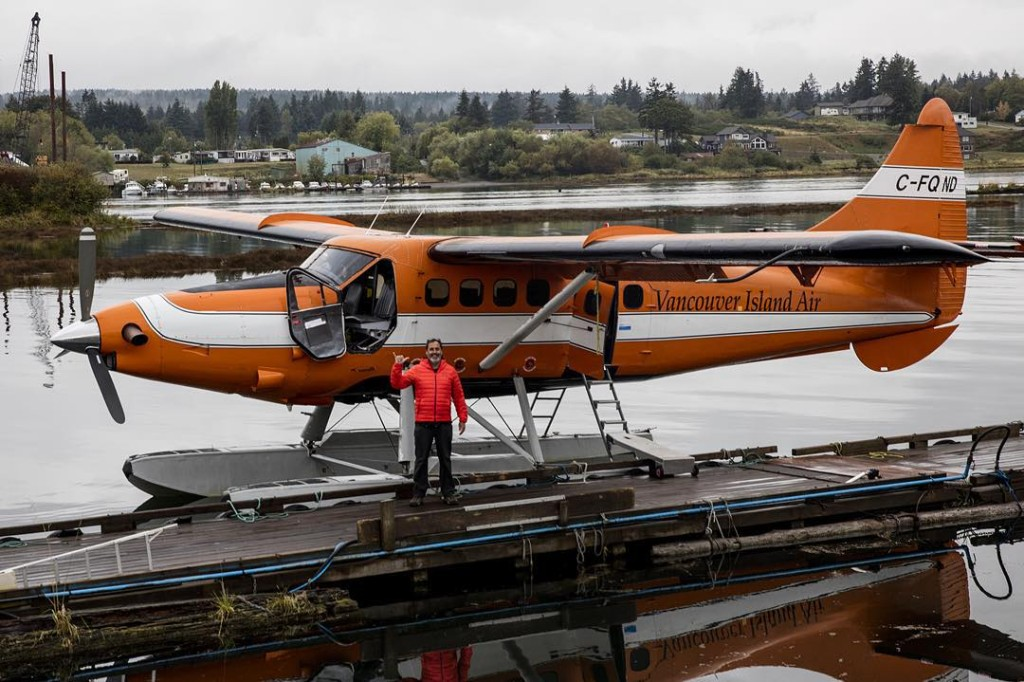 A man stands in front of an orange seaplane.