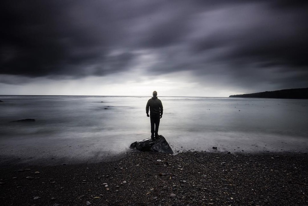 Silhouette of a man standing on a rock on a beach under a dark sky.