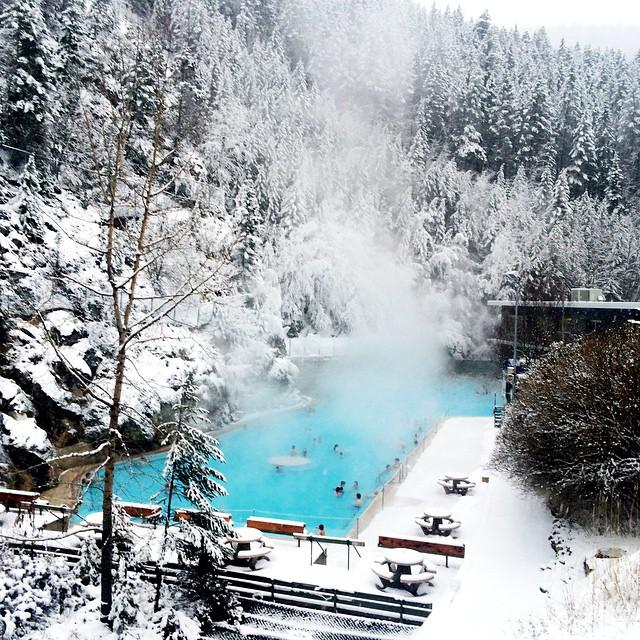 A bright blue hot spring is surrounded by a snowy landscape