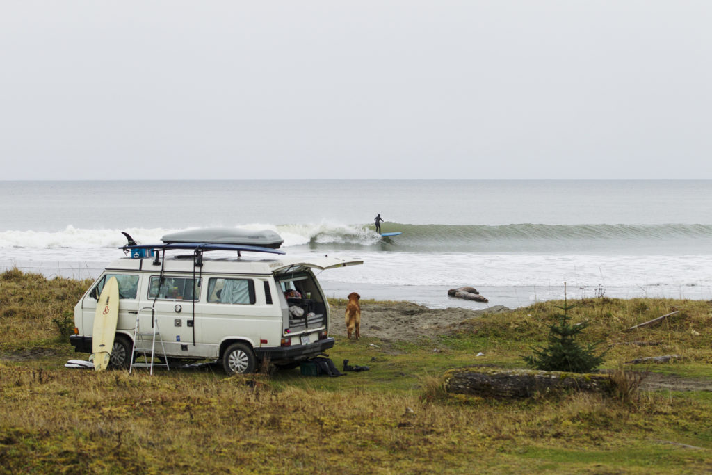 A VW van is parked on the beach, overlooking a surfer riding the waves.