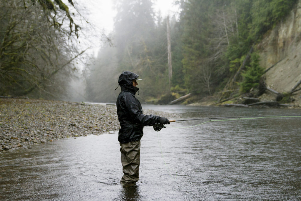 A man stands in a river, fishing.