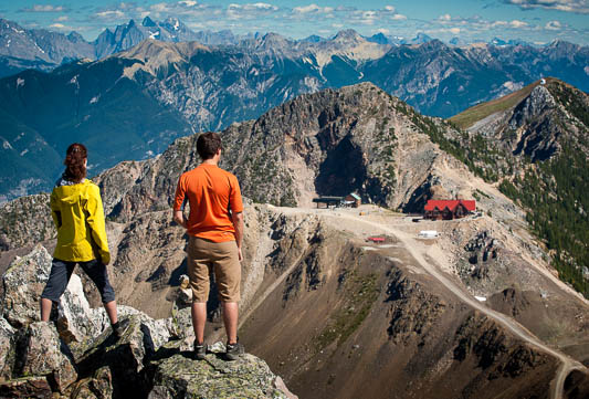 Two hikers stand on a rocky mountain peak, overlooking a resort nestled in the landscape.