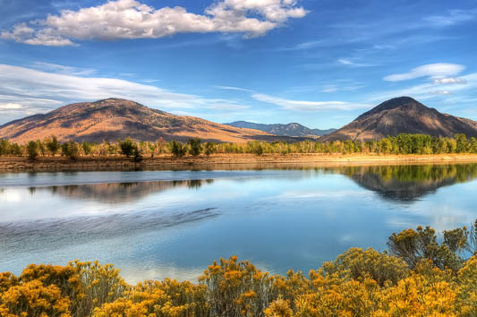A rolling landscape is reflected in calm waters under a bright blue sky.