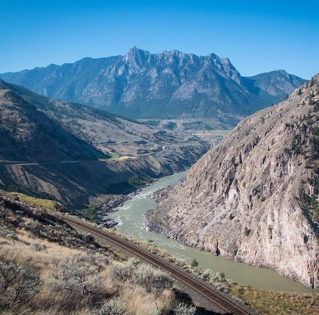 Train tracks follow a river through a rocky mountain landscape.