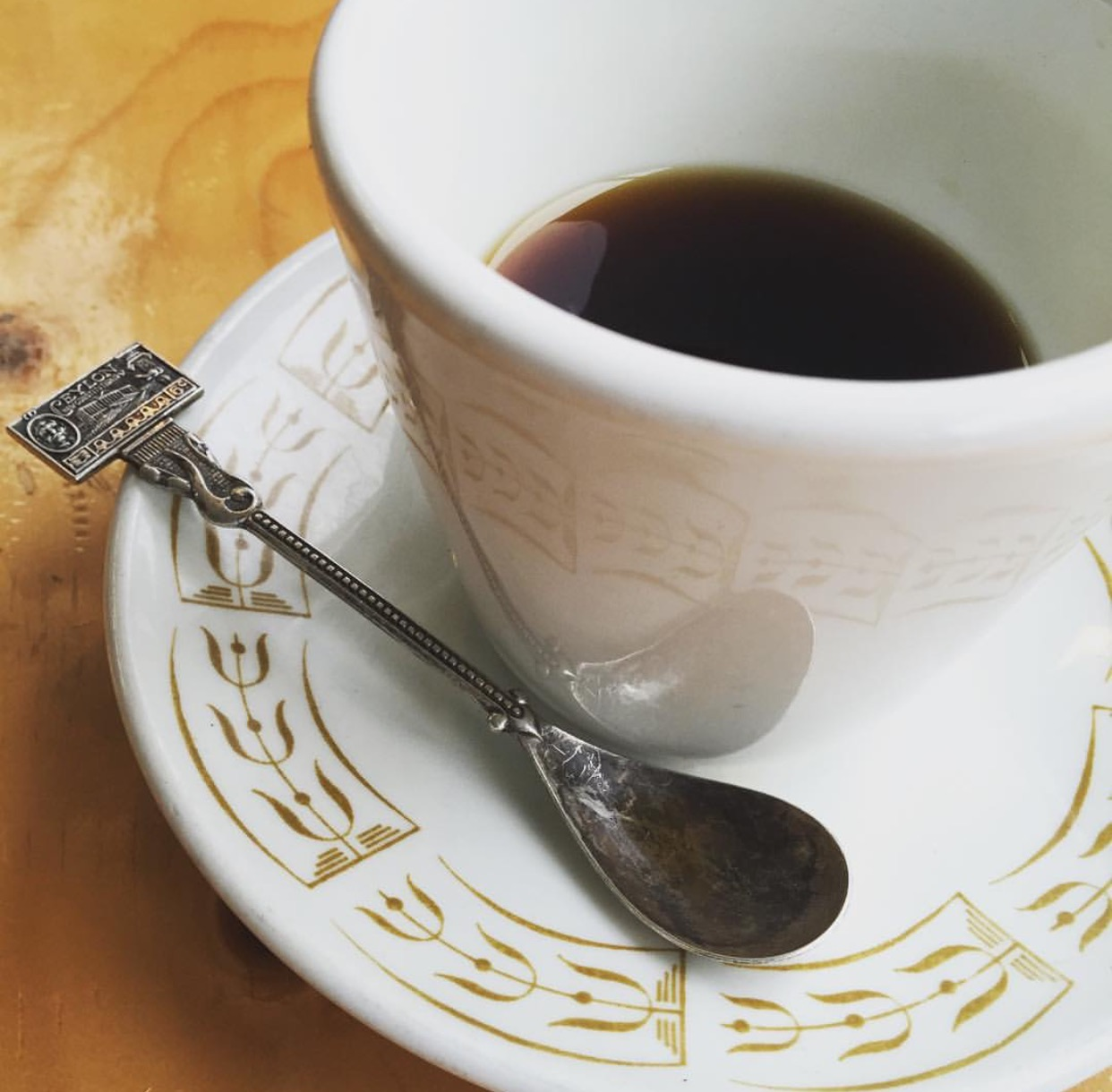 A cup of coffee on a white and gold saucer with a small spoon.