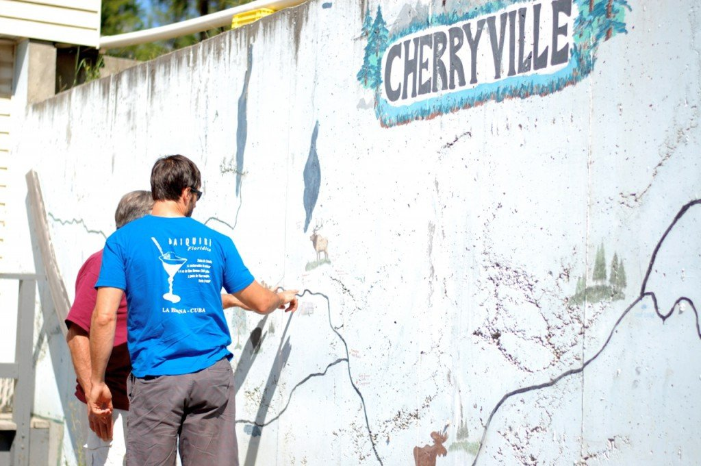 "Two men stop to look at a map painted on a wall that says ""Cherryville""."