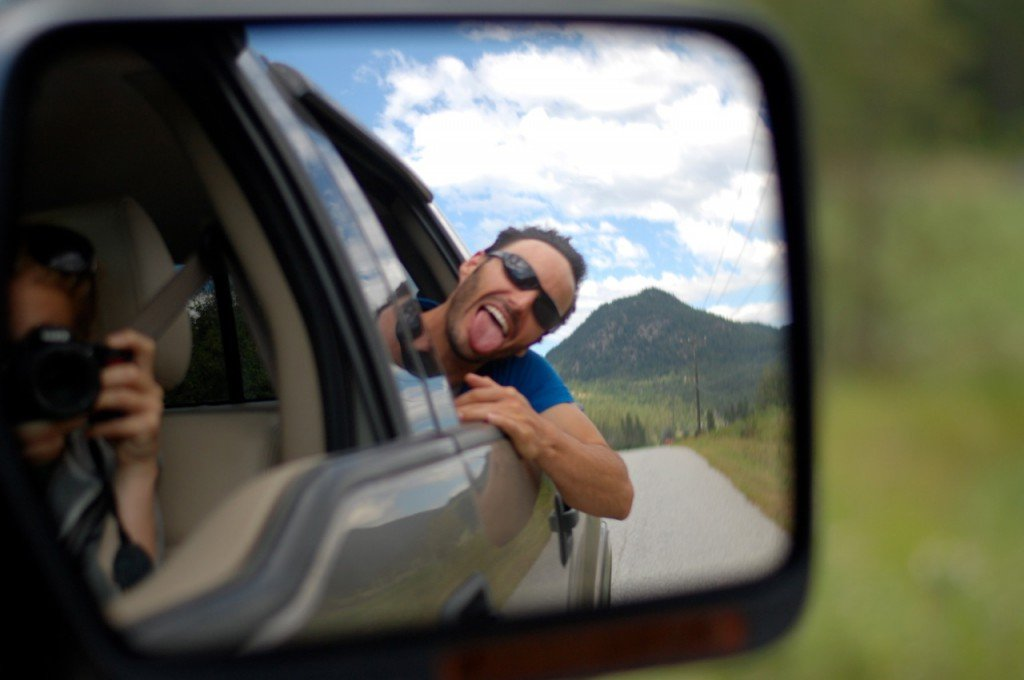 A man sticks his head out of a car window and sticks his tongue out in the reflection of the side mirror.