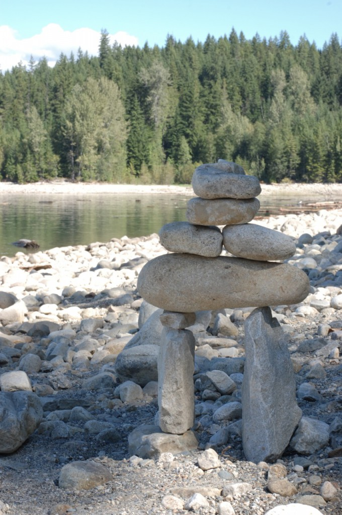 A mini-inukshuk sits on a rocky beach.