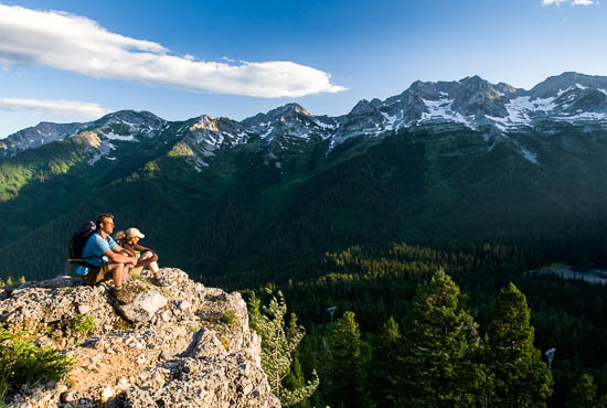 Two hikers sit at the edge of a cliff, taking in the views of the snow-capped mountains.