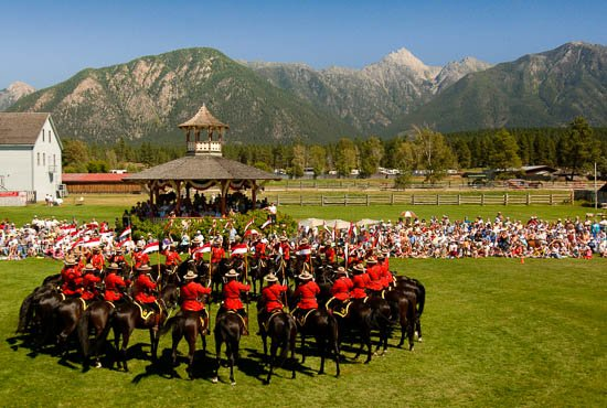 A large crowd sits and watches a circle of RCMP officers on horseback.