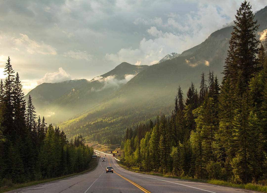 A highway stretches past a stunning mountainous landscape at sunset.