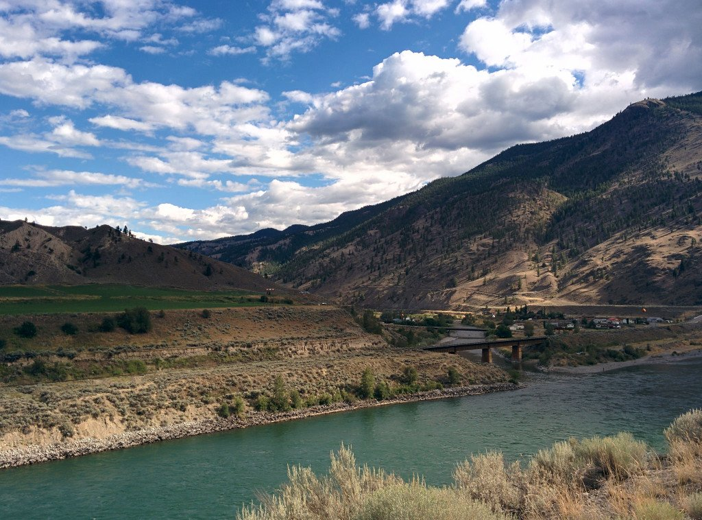 A rolling mountainous landscape and a dark green river.