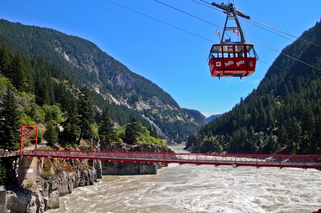 A red airtram travels above a red bridge and rushing waters.