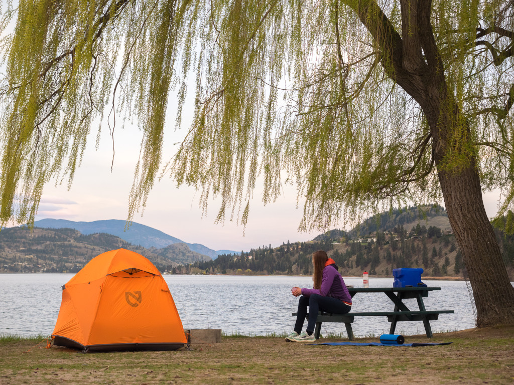 A woman sits at a picnic tale next to an orange tent overlooking the water.