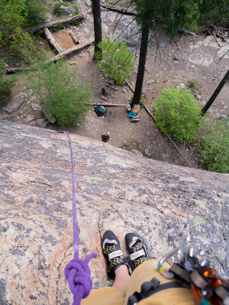 A rock climber's view from the top of a climb.