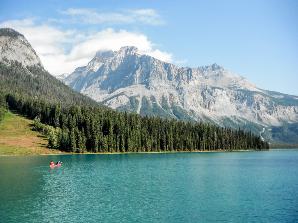 A canoe travels across turquoise waters towards snow-covered mountains.
