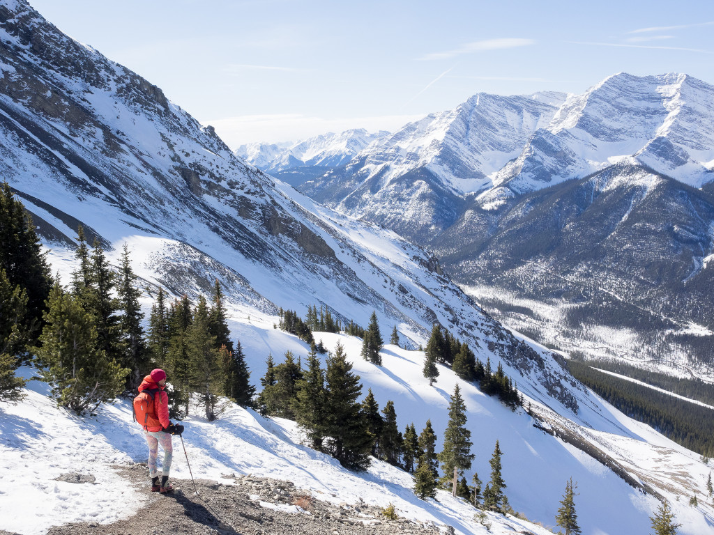 A woman hikes down the side of a snow-covered mountain.