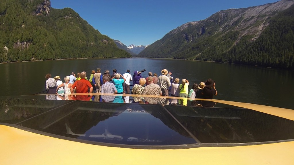 Group of people looking for wildlife from a boat in the Khutzeymateen Grizzly Bear Sanctuary.