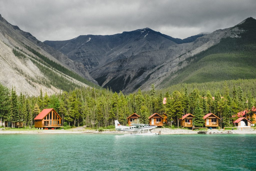 A seaplane docked at a beach lined with wood lodges nestled at the base of a rocky mountain range.