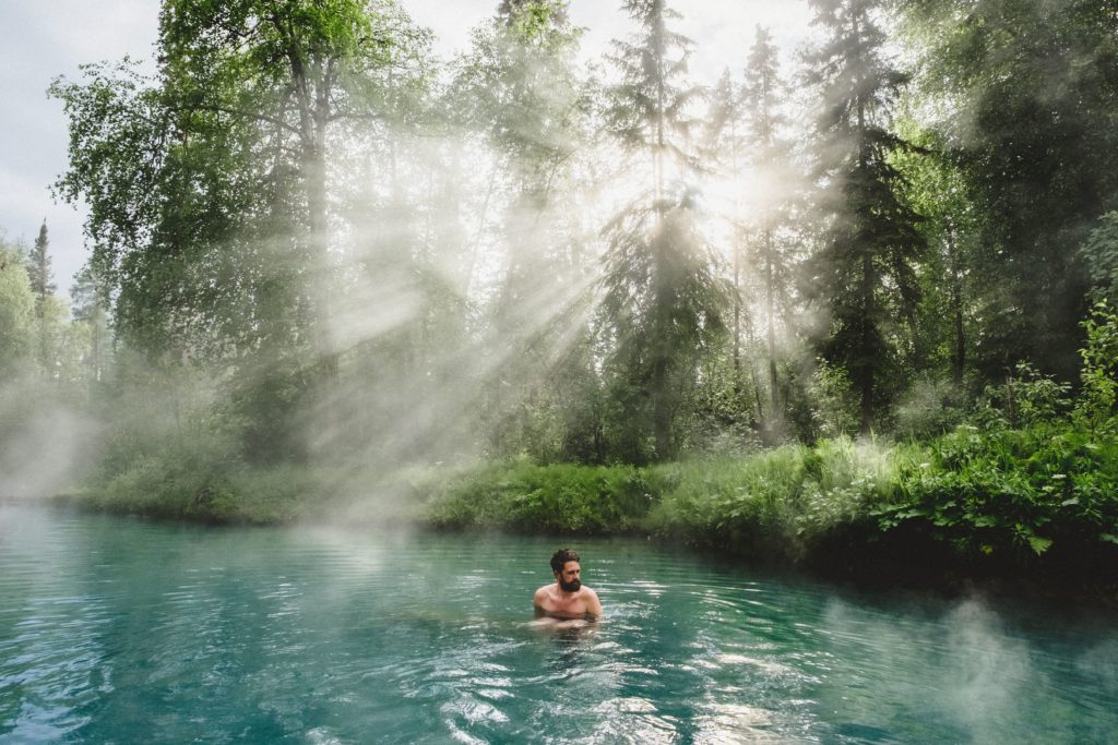 A man relaxes in a turquoise hot spring drenched in sunlight.