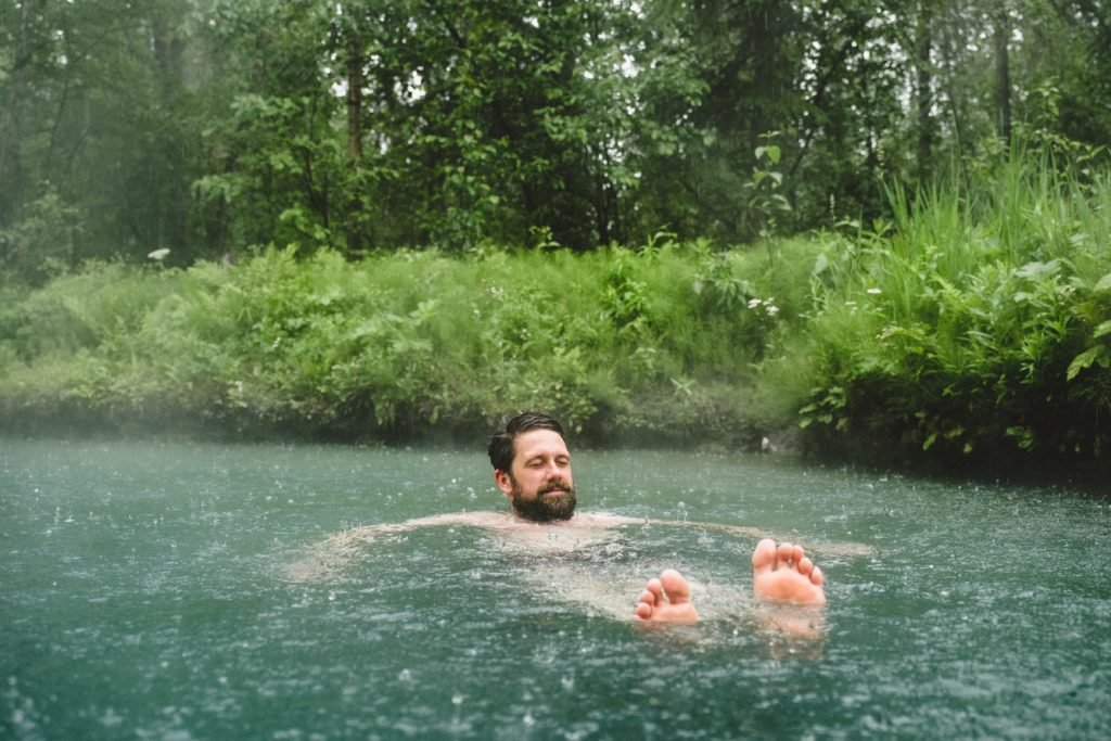 A man floats in a hot spring in the rain.
