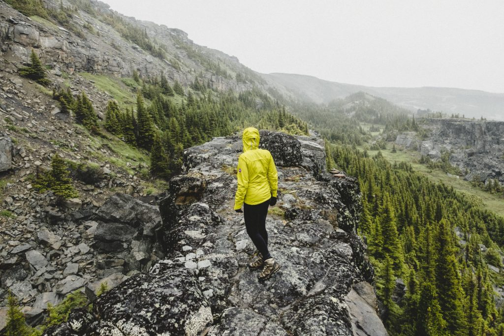 A woman in a yellow rain jacket hikes through a rocky landscape.