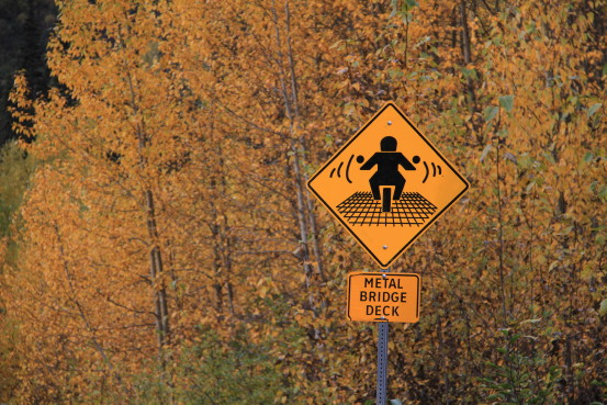 Metal bridge deck warning sign for motorcycles on the Alaska Highway