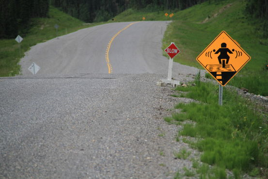 Gravel road warning sign for motorcycles on the Alaska Highway