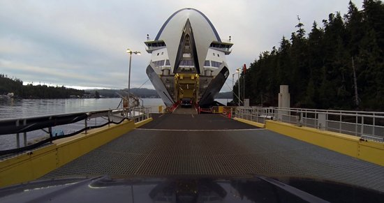 Cars driving onto a large ferry.