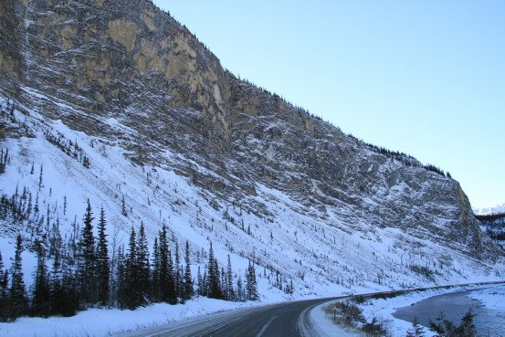 A highway winds past a snow-covered rocky mountain.