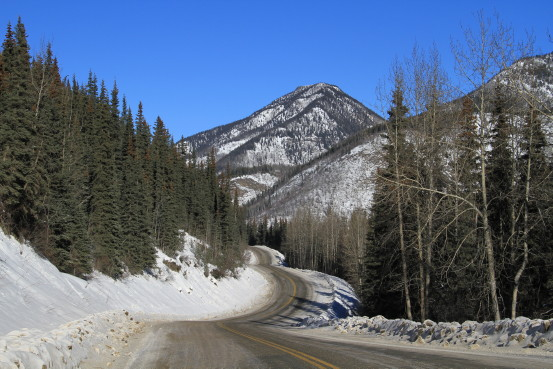 A highway leads towards a snow-covered mountain.