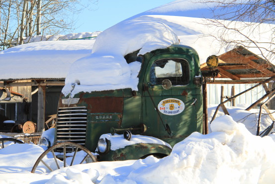 A green vintage truck is covered in snow.