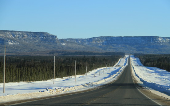 A long stretch of highway, lined on both sides with snow.
