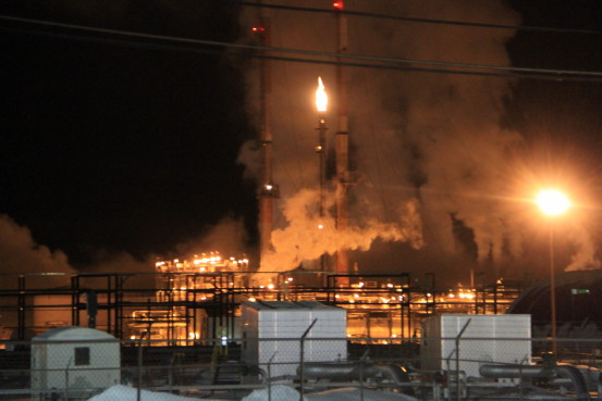 A gas processing plant is aglow under an evening sky.