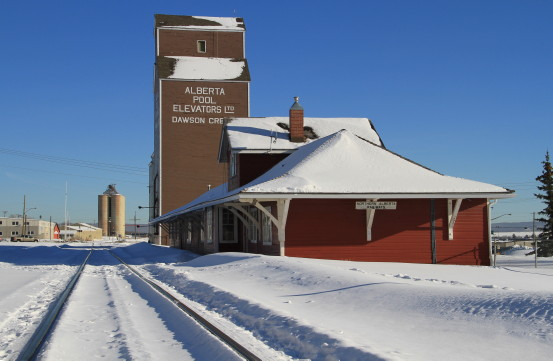 """A snow-covered building with the words """"Alberta Pool Elevators, Dawson Creek"""" on the side."""