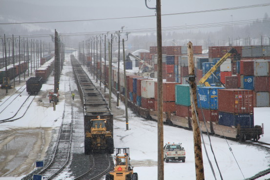 A bustling railway yard covered in snow.