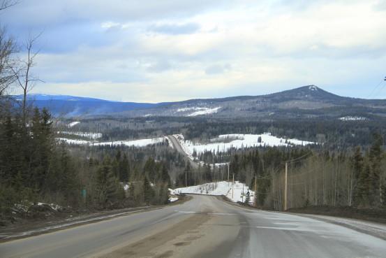 A highway travels across a rolling winter landscape.