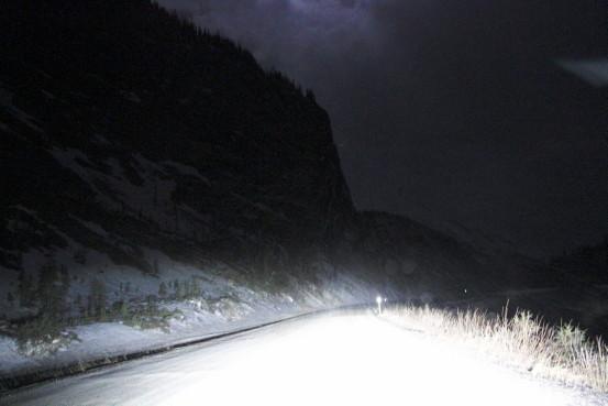 Headlights illuminate a snow-covered highway at night.