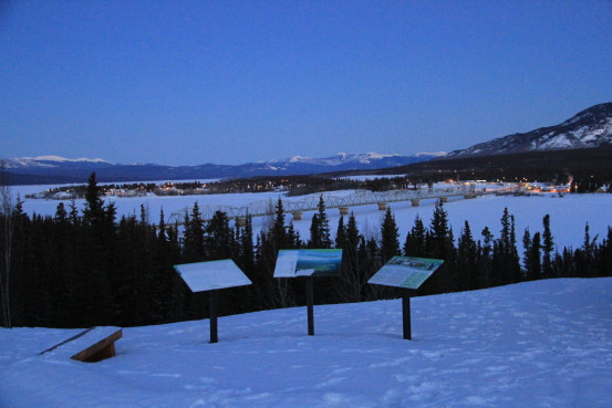 A snowy landscape and three informational placards awash in blue light.