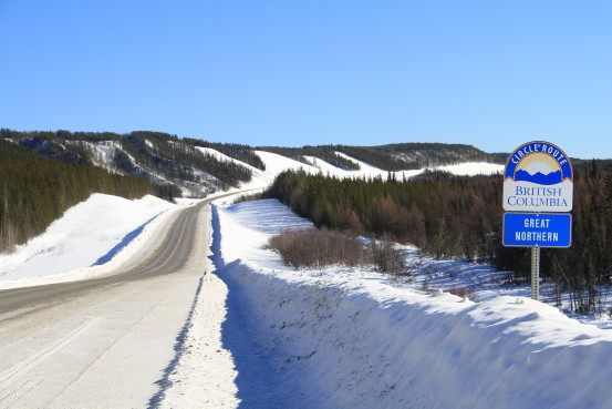 """A snowy highway with a sign that says """"British Columbia Great Northern Circle Route."""