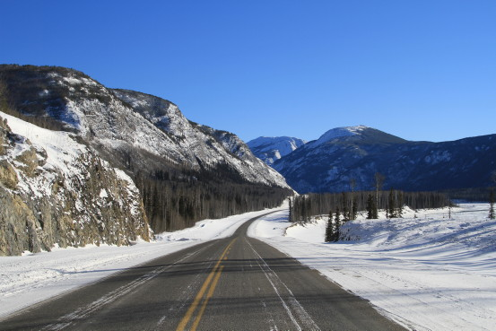 A highway winds through a snow-covered mountainous landscape.
