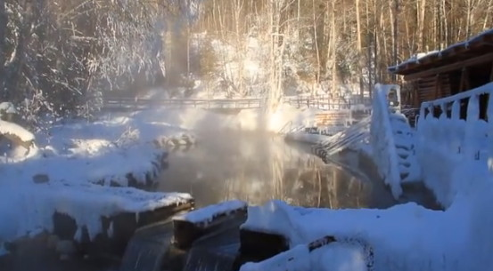 Steam rises off a hot spring, surrounded by a snowy landscape.