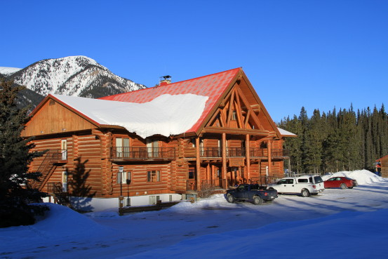Cars are parked at a snow-covered log cabin.