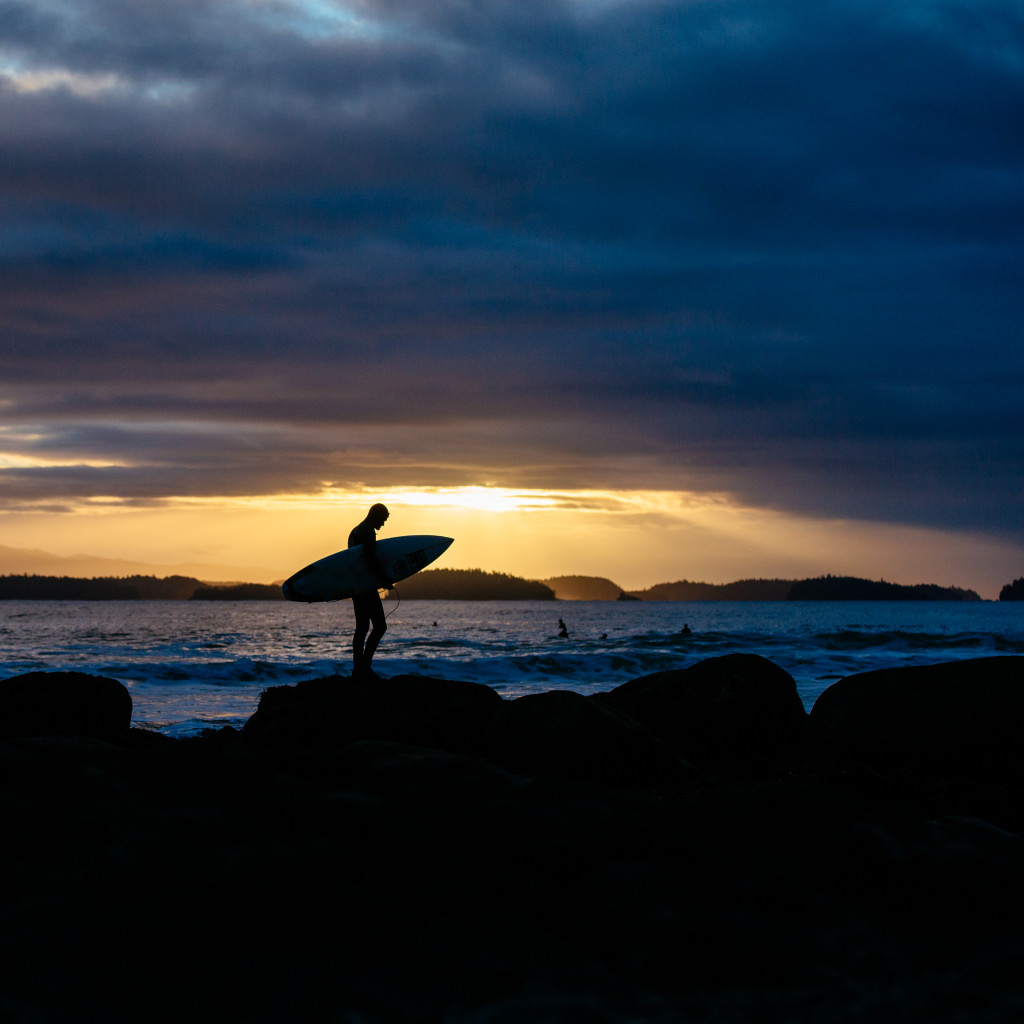 A silouette of @raphbruhwiler of Bruhwiler Surf School heading out for a sunrise surf with dark clouds and orange skies above by @jeremykoreski