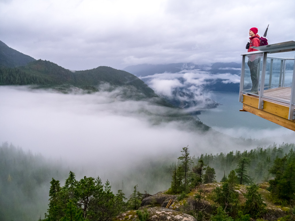 A hiker in a red jacket looking out over the trees and misty fog and clouds on top of the wooden viewing platform at the top of the Sea to Sky Gondola.
