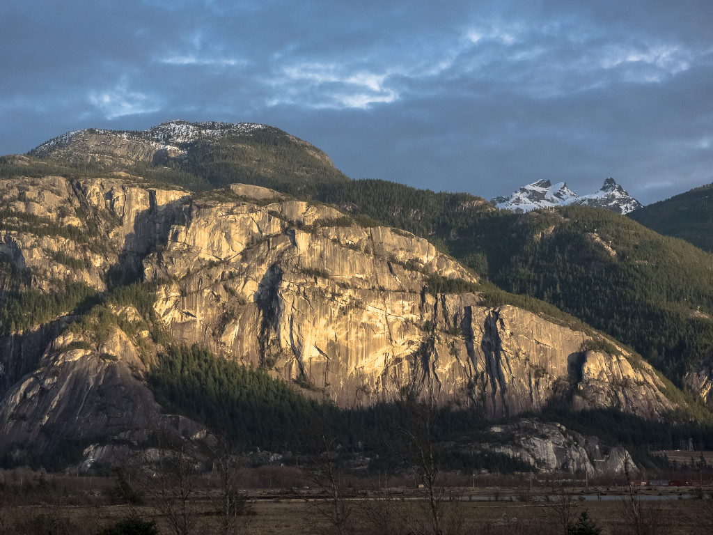 The rocky bluffs of the Stawamus Chief from the Squamish Estuary at sunset with dark stormy clouds above.